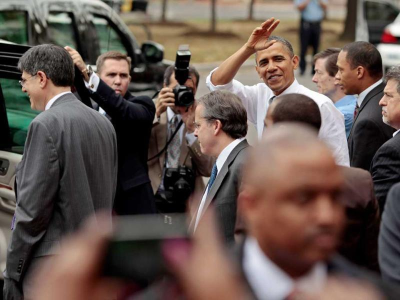 US President Barack Obama waves to people on the street after eating at Good Stuff Eatery on Pennsylvania Avenue in the Capitol Hill neighborhood in Washington.