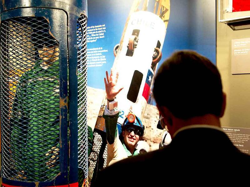 A reporter looks at the display of the Phoenix rescue capsule (L) on display during a press preview for the Against All Odds exhibition commemorating the rescue of 33 Chilean miners, at the Smithsonian National Museum of Natural History in Washington, DC.