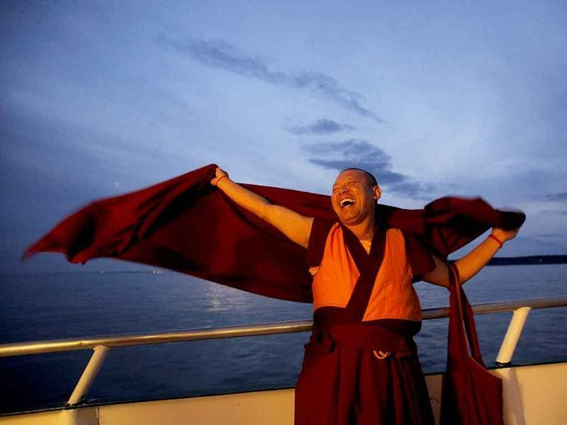 Buddhist monk Geshe Tenley laughs as his robes flap in the breeze on the bow of a boat during the release of lobsters back into the ocean on 'Chokhor Duchen', or the anniversary of Buddha's turning of the Dharma Wheel, in the waters off Gloucester, Massachusetts.