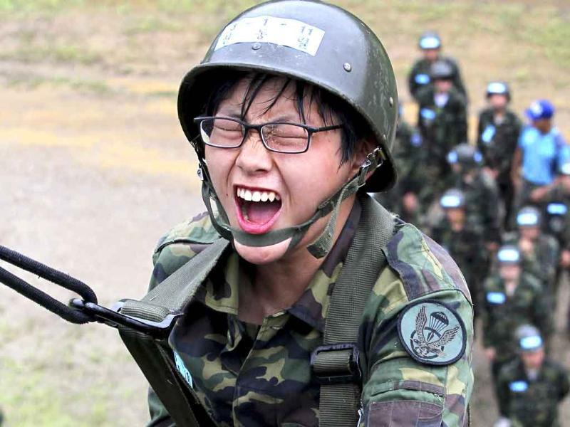 A South Korean high school student shouts as he waits to jump from a tower during a summer survival camp at a ranger-commando force unit in Seoul, South Korea.