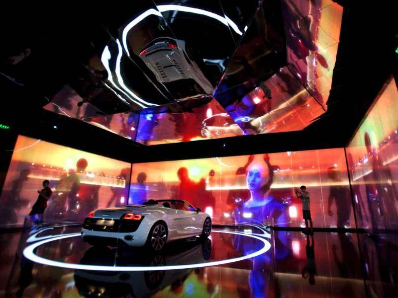 A man takes pictures of a new Audi R8 convertible on display in a room during a show in Beijing.
