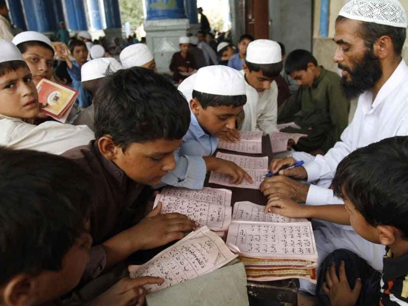 Young Afghan children take lessons on the Quran from their teacher during the Muslim holy month of Ramadan at a mosque in the city of Jalalabad, Afghanistan.