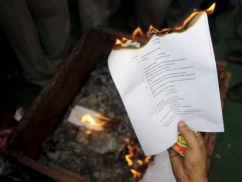 A supporter of anti-corruption activist Anna Hazare burns a copy of the Lokpal Bill during a protest on the outskirts of New Delhi
