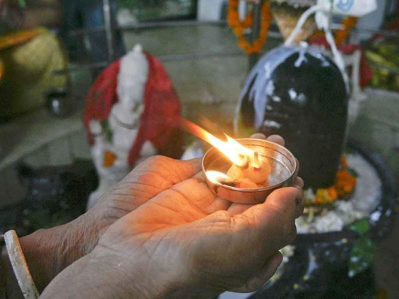 A devotee holds an oil lamp next to a Shivling (a symbol of Lord Shiva) as she worships during the Naag Panchami festival at a temple in Chandigarh.
