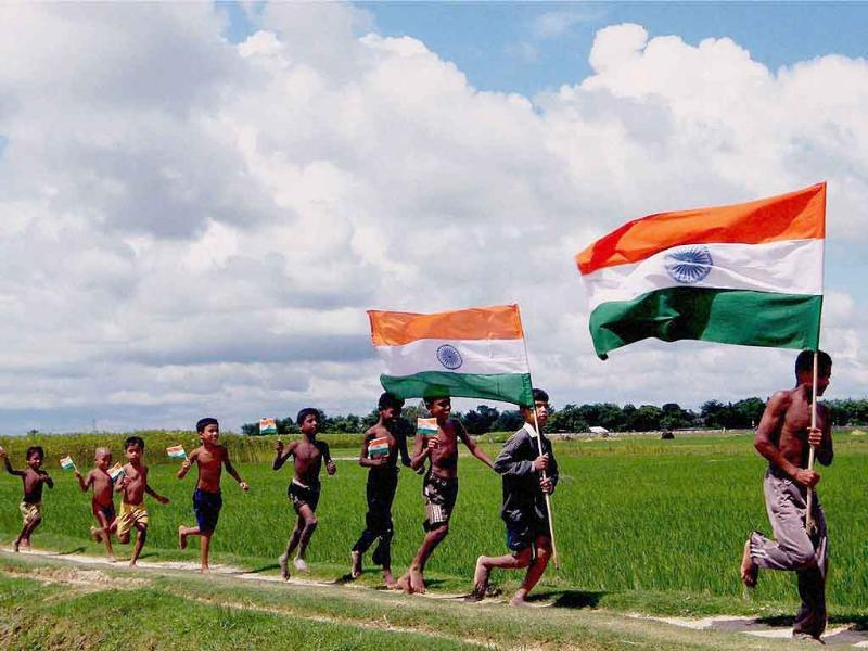 Children holding tricolours, running along a paddy field ahead of Independence day celebrations at Balurghat in South Dinajpur