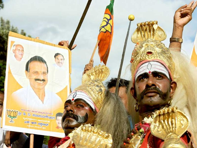 Traditional dancers of Karnataka state dressed in traditional costumes dance alongside a poster of newly appointed Chief Minister of Karnataka D V Sadananda Gowda in Bangalore. Sadananda Gowda was sworn in to replace ex chief minister B S Yeddyurappa had who resigned on July 31 after he was accused of being in the center of a $3.6 billion mining fraud.