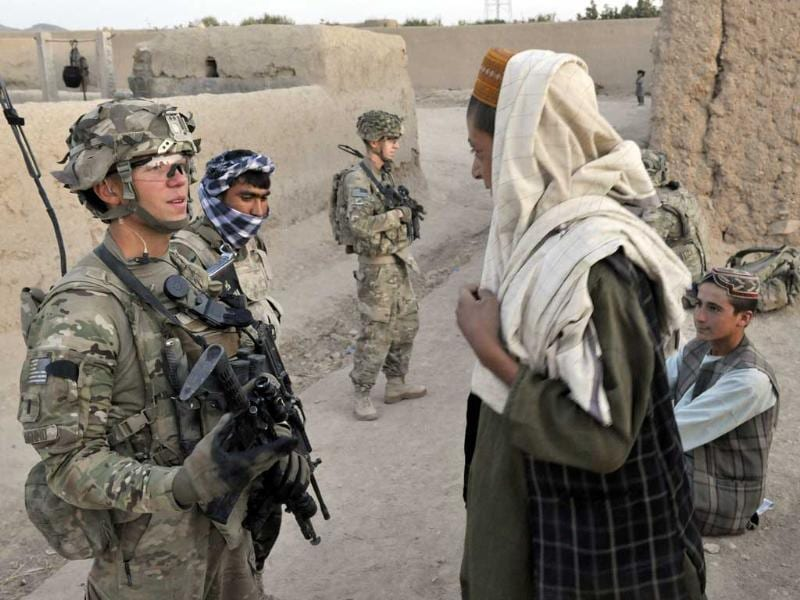 US Army Lieutenant Joseph DeNenno from the 2nd Platoon, Charlie Company, 2-87, 3BCT under Afghanistan's International Security Assistance Force speaks to Afghan children during a joint security patrol with Afghan National Army soldiers in the center of Kandalay village, in Kandahar province southern Afghanistan. The 140,000 strong US-dominated international military in Afghanistan is engaged in a massive drive to train Afghan police and army to take over before all foreign combat troops leave the country in 2014.