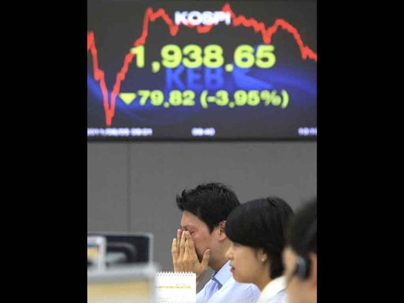 A currency trader reacts in front of screens showing the Korea Composite Stock Price Index at the Korea Exchange Bank headquarters in Seoul, South Korea.