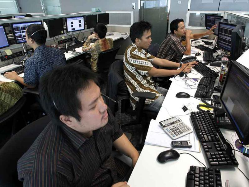 Traders monitor stock prices at Profindo International Securities in Jakarta, even as Indonesia's stock market fell more than 5% on global cues.