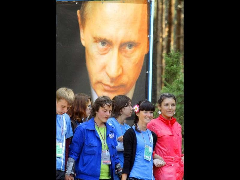 Members of pro-Kremlin movement 'Nashi' pass a poster of Putin at the Seliger youth educational forum near Lake Seliger, Tver region, Russia.