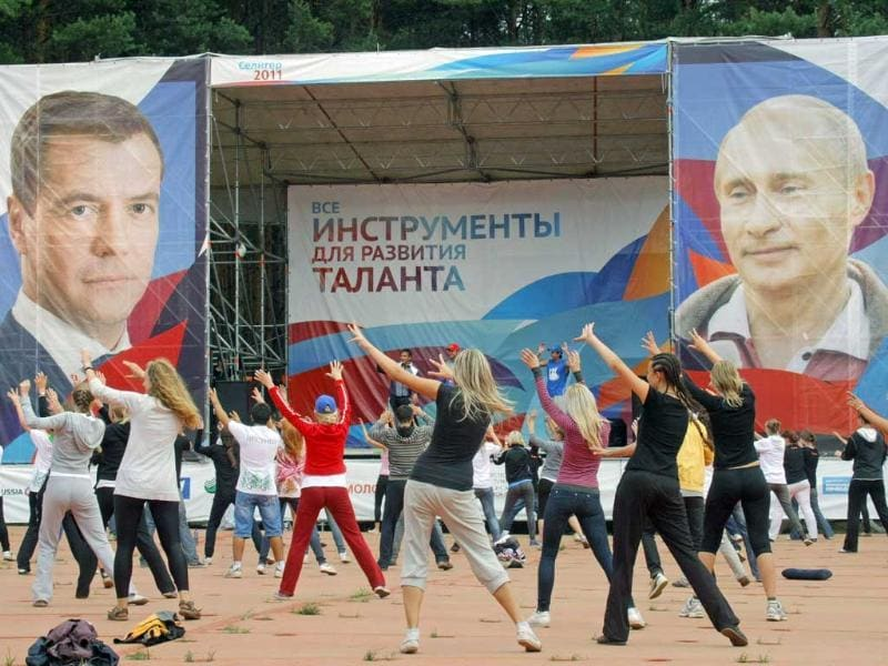 Pro-Kremlin youth activists dance in front of a portrait of Russian President Dmitri Medvedev and Prime Minister Vladimir Putin.