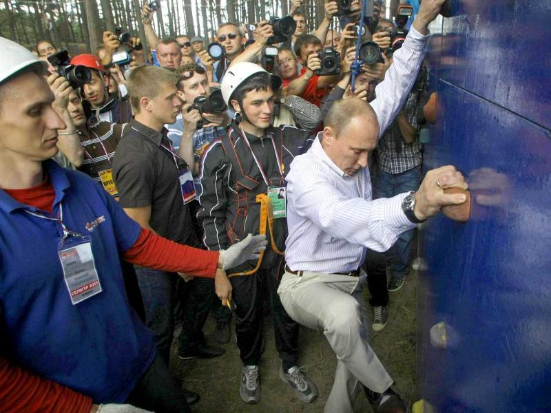 Russian Prime Minister Vladimir Putin climbs on a climbing wall during his visit to the summer camp of the pro-Kremlin youth group