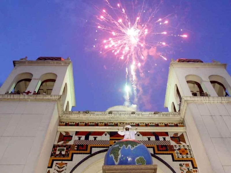 Fireworks explode over a statue of Jesus Christ, known as the Divine Saviour of the World in El Salvador, during