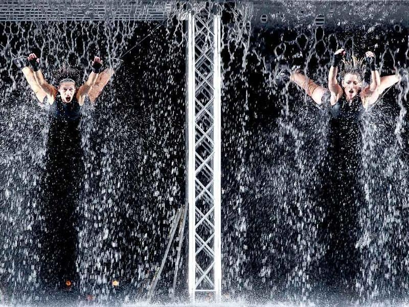 Dancers of Italian company Materiali Resistenti Dance Factory perform suspended from cables during waterwall show at Lisbon's Comercio square.