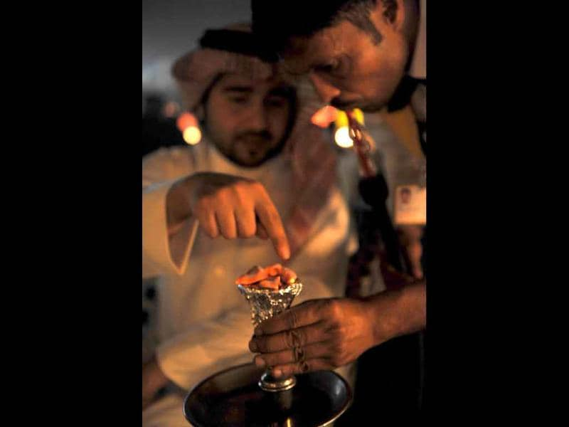 A Saudi man speaks to a waiter as he prepares a waterpipe at a coffee shop in western Riyadh hours before dawn marking the start of a fasting day during the holy month of Ramadan.