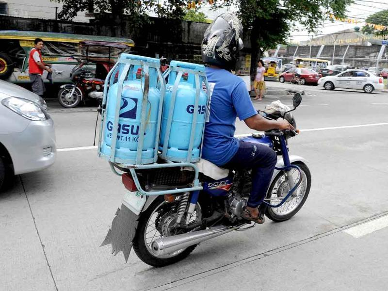 A man delivers cylinders of liquefied petroleum gas in Manila.