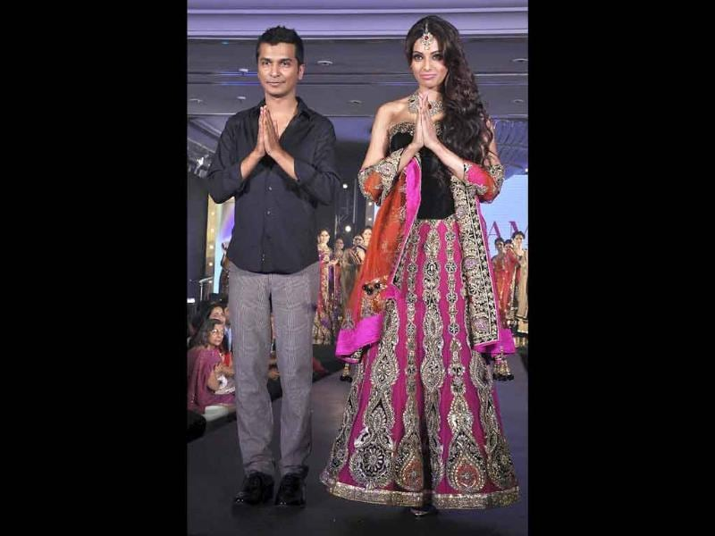 Gorgeous Bipasha Basu (R) gestures on the ramp while displaying creations by designer Vikram Phadnis (L) during the show. (AFP)