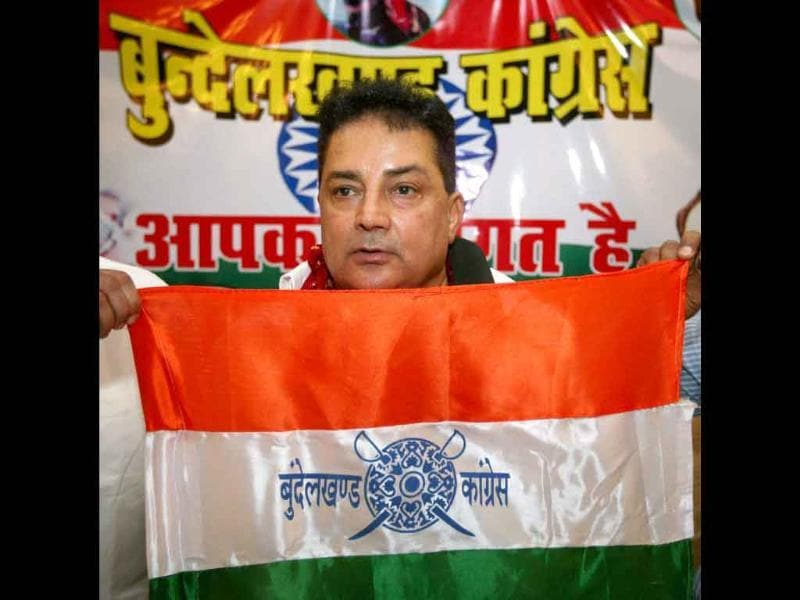 Bundelkhand Mukti Morcha chief Raja Bundela shows the flag of his newly launched party Bundelkhand Congress at a press conference in Lucknow.