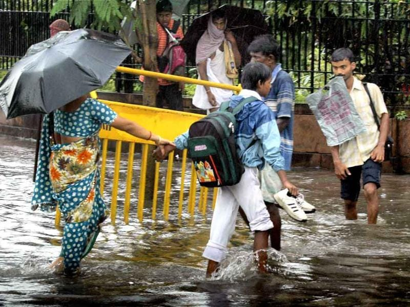 A school boy with his mother crossing a waterlogged road after rains in Kolkata.