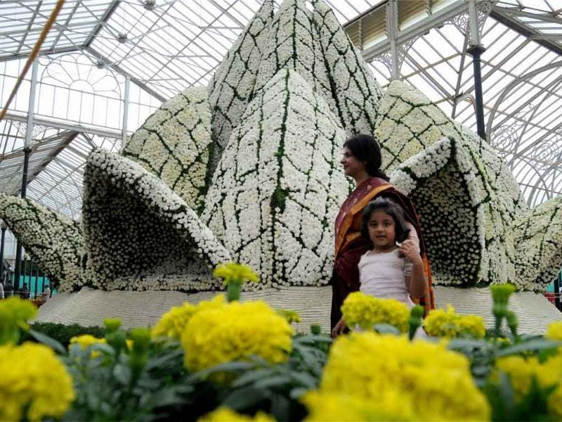 A mother and her kid admire the replica of Lotus Temple of Delhi, created by using various flowers at the Annual Flower show for the Independence Day in Bangalore.