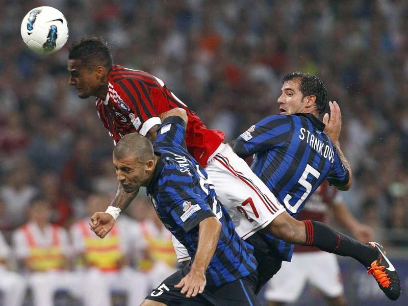 AC Milan's Kevin-Prince Boateng (top) dives for a header as he is challenged by Inter Milan's Walter Adrian Samuel (bottom) and Dejan Stankovic during their Italian Super Cup soccer match at the National Olympic Stadium in Beijing.