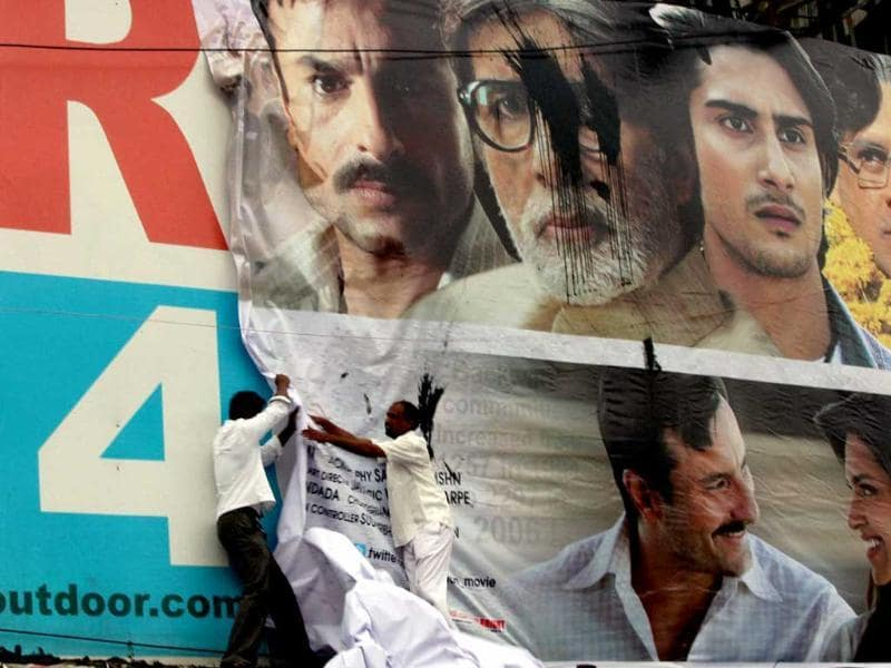 Activists of Samta Parishad remove a poster of the film Aarakshan during a protest against its screening in Mumbai.