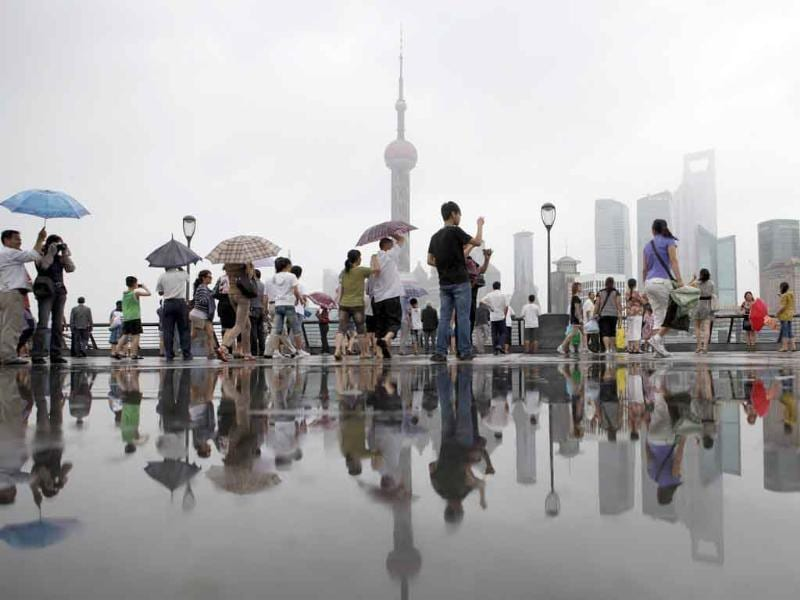 People walk after the rain along the Bund near the Huangpu River, as Typhoon Muifa passes, near the coastal area of Shanghai.