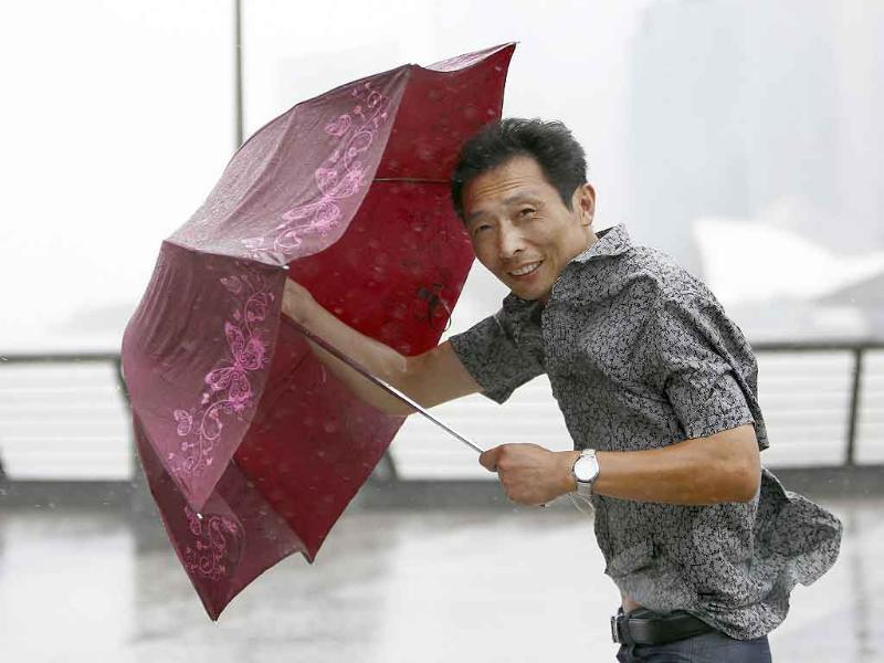 A man tries to hold onto his umbrella as Typhoon Muifa passes near the coastal area of Shanghai.