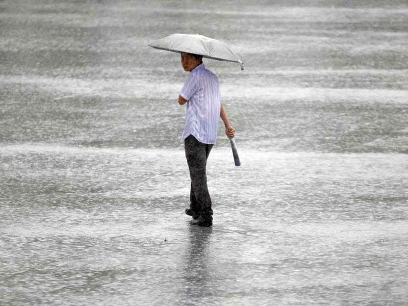 A man carries an umbrella while walking in the rain, as Typhoon Muifa passes, near the coastal area of Shanghai.