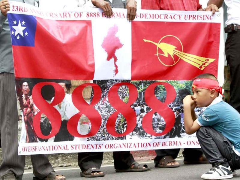 A boy squats next to a banner as human rights activists gather to protest against the ruling military junta during a rally marking the 23rd anniversary of the