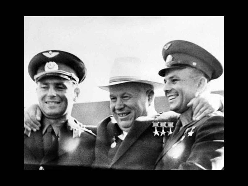 Soviet leader Nikita Khrushchev (C) embraces Soviet cosmonauts Yuri Gagarin (R) and Gherman Titov (L) after Titov arrived from the Vostok 2 space mission, on Red Square in Moscow, on August 9, 1961.