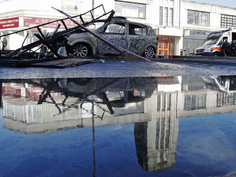 The remains of a burned police car is reflected in water after riots in Tottenham, north London.