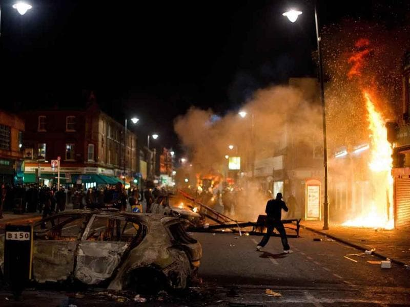 A shop and police car burn as riot police try to contain a large group of people on a main road in Tottenham, north London.