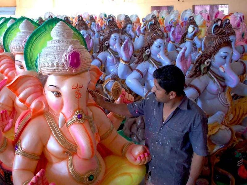 An artist gives finishing touches to the idols of Lord Ganesha ahead of the Ganesh Chathurti festival in Karad, Maharashtra.