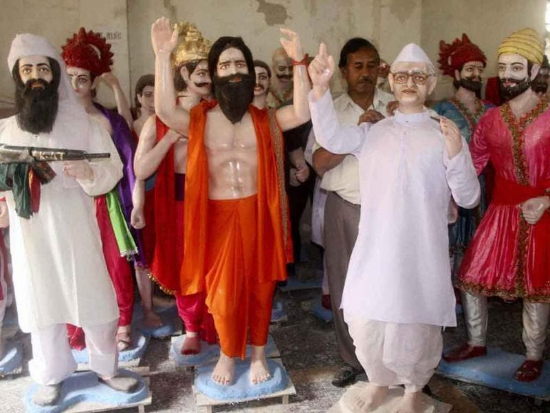 Artist Satish Taru adjusts the attire of a statue of social activists Anna Hazare, right, beside statues of Baba Ramdev, center, Osama bin Laden, left, among others at his studio in Pune.