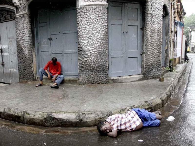 Two men intoxicated with alcohol rest by a pavement as it rains in Kolkata.
