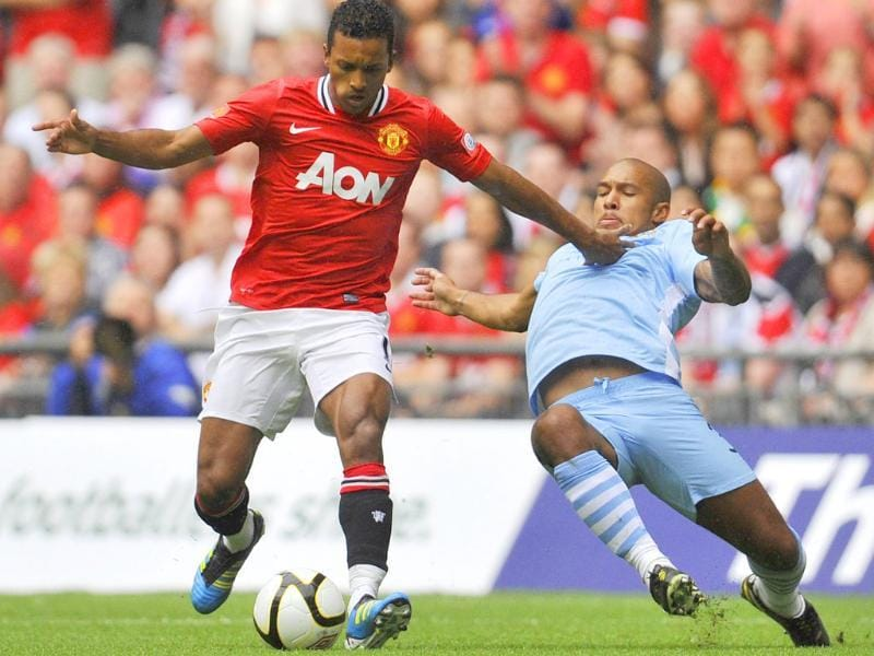 Manchester United's Nani (L) is challenged by Manchester City's Nigel De Jong during their FA Community Shield soccer match at Wembley Stadium in London.