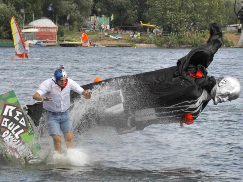 A competitor with his makeshift craft that features Soviet founder Vladimir Lenin falls into the Moskva River during the Red Bull Flugtag Moscow 2011.