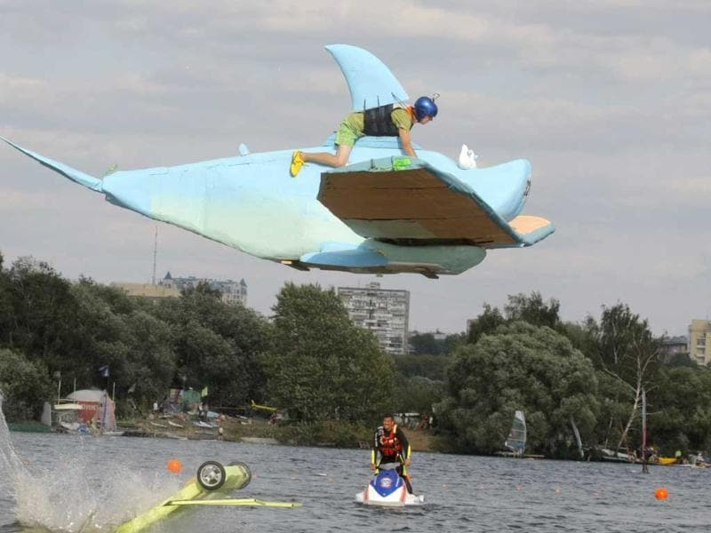 A competitor jumps with his makeshift aircraft as they plummet into the Moskva River during the Red Bull Flugtag Moscow 2011 competition.