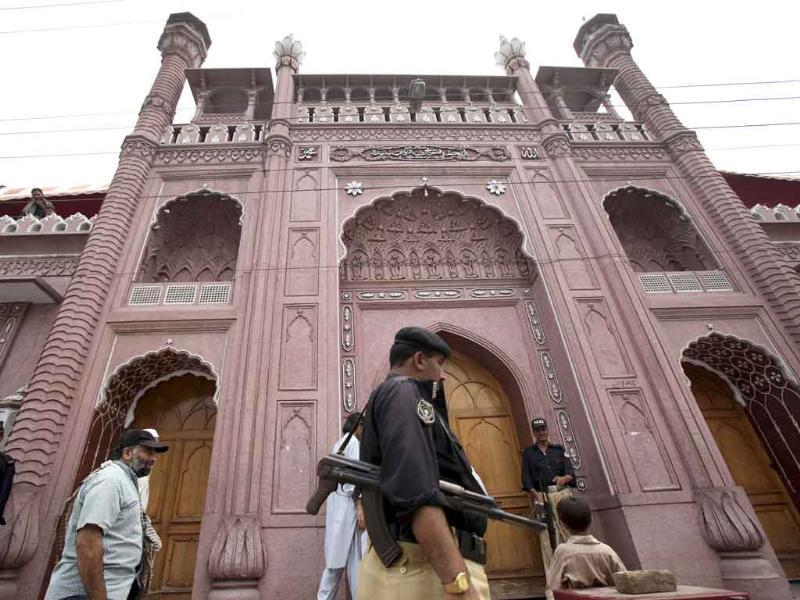 Pakistani police officers guard a local mosque as people attend prayers during the month of Ramadan in Peshawar, Pakistan.