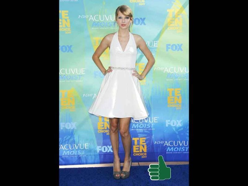Taylor Swift gets it absolutely right in a white halter Rafael Cennamo dress, Neil Lane jewels and Fendi footwear.
