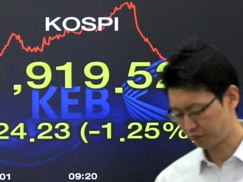 A currency trader passes by a screen showing the Korea Composite Stock Price Index at the Korea Exchange Bank headquarters in Seoul, South Korea.