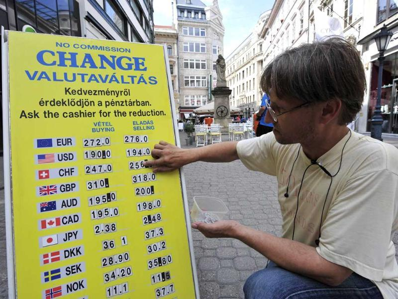 A employee changes currency rates on an information board in front of an exchange office in downtown Budapest.