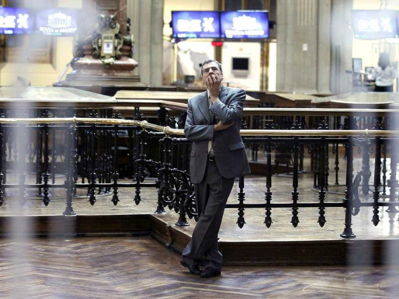 A trader is seen through a window as he looks at screens at the bourse in Madrid.