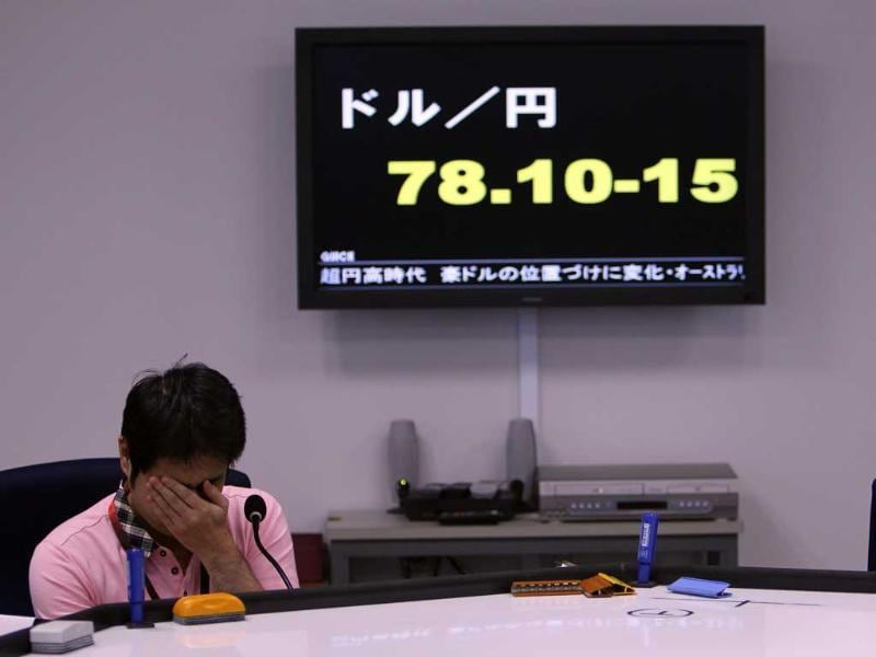 A money trader waits for calls from clients during the morning trading at a money brokerage in Tokyo.