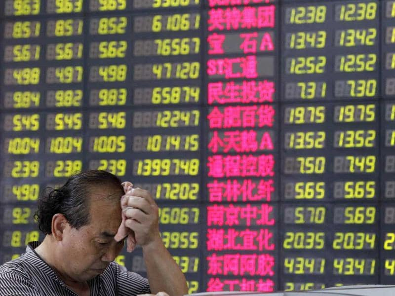A man reacts in front of an electronic board showing stock information at a brokerage house in Shanghai.
