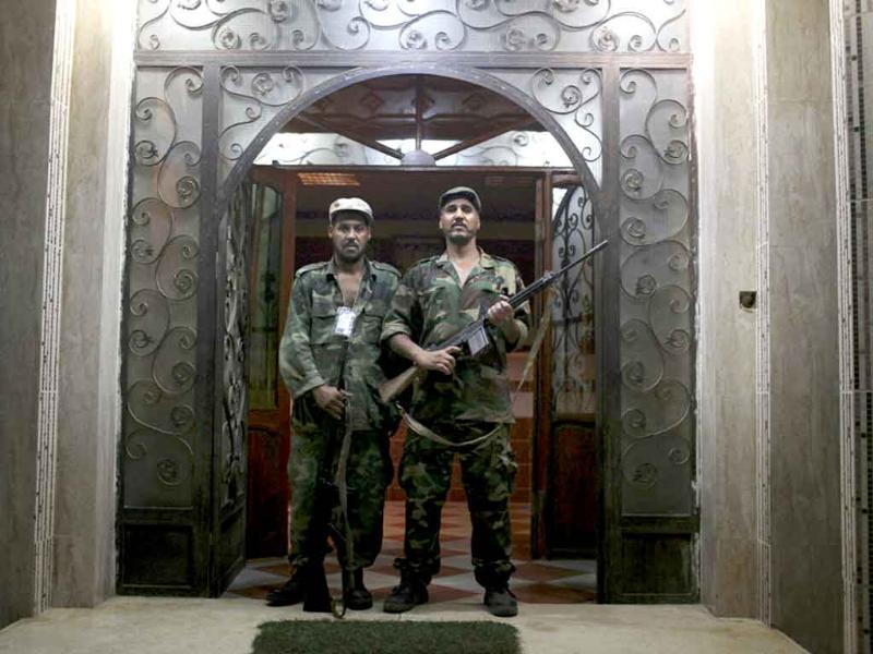 Muhamed Ali, 40, a truck driver (L) and Hosiena Alimi, 42, a cattle seller, both working for security since the beginning of the country's civil war in February, pose for a photo in front of a hotel at the rebel-held town of Benghazi, Libya.