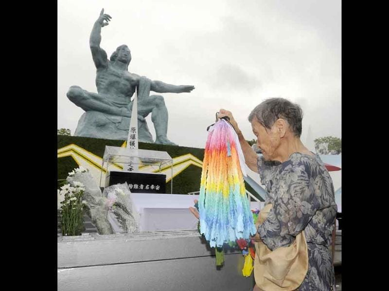 A woman offers thousand paper cranes in front of the Statue of Peace at Nagasaki Peace Park in Nagasaki, southern Japan.