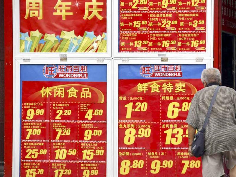 A shopper looks at a board displaying food prices as he walks into a shopping mall in central Beijing.