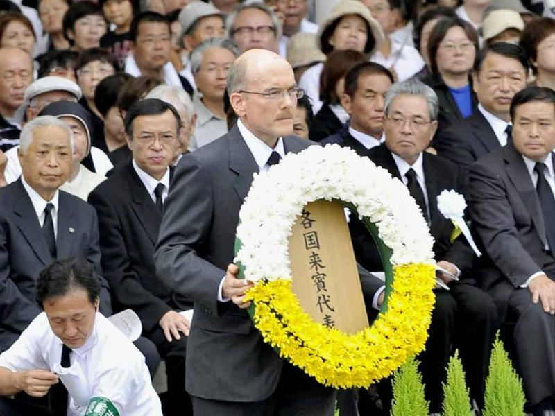 James Zumwalt, deputy chief of mission at the US Embassy in Tokyo, carries a wreath to the altar set up in Nagasaki Peace Park in Nagasaki, southern Japan.